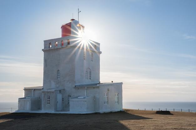 Sunburst świeci przez latarni dyrholaey w islandii z oceanu atlantyckiego