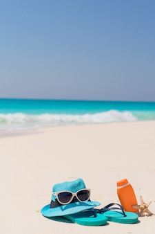 Suncream butelki, gogle, rozgwiazda i okulary przeciwsłoneczni na białym piasek plaży tle oceanu