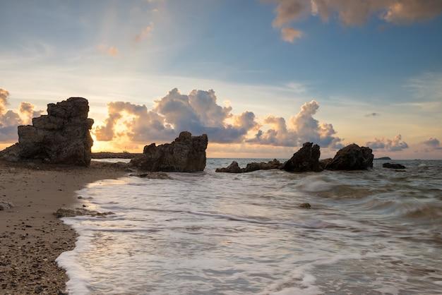 Sunrise seascape z naturalnego kamienia łuku i fala morza ruchu rayong plaży, tajlandia. znany cel podróży i wczasowicz w siam, tropikalnym kraju.