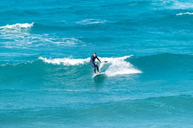Sup stand up surfujący mężczyzna z wiosłem w błękitnym morzu.
