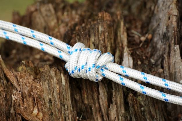 Supeł na sznurku na drewnianym tle.