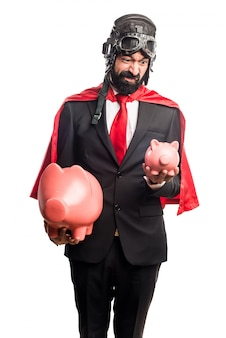 Super bohater biznesmen trzyma piggybank