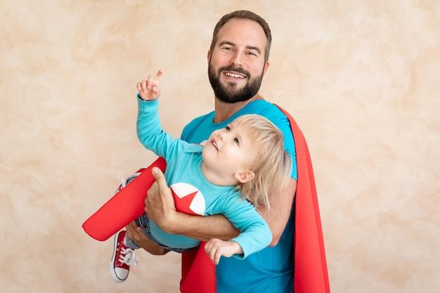 Super bohatera człowieka i dziecka w domu. ojciec i syn superbohatera bawią się razem.