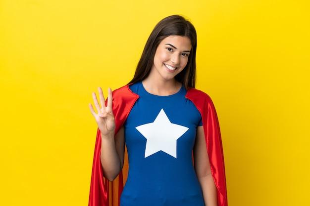 Super bohaterka brazylijska kobieta na białym tle na żółtym tle szczęśliwa i licząca cztery palcami