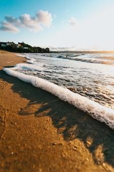 Super zbliżenie niektórych pływów z bąbelkami na plaży podczas super kolorowego słońca