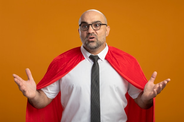 Superbohater biznesmen w czerwonej pelerynie i okularach, mylić z podniesionymi rękami stojąc na pomarańczowej ścianie