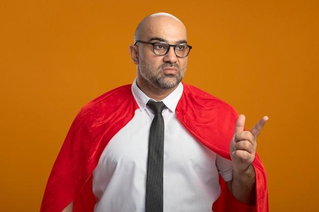 Superbohater biznesmen w czerwonej pelerynie i okularach patrząc na bok z poważną twarzą wskazującą palcem wskazującym na coś stojącego nad pomarańczową ścianą