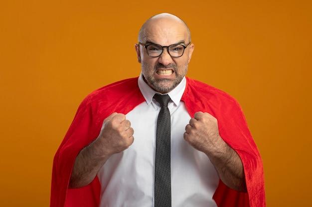 Superbohater biznesmen w czerwonej pelerynie i okularach zaciska pięści do szaleństwa
