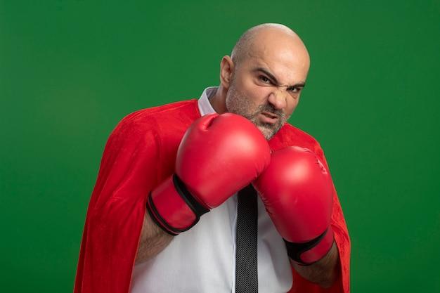Superbohater biznesmen w czerwonej pelerynie i rękawicach bokserskich patrząc z przodu z poważną twarzą gotową do walki stojąc nad zieloną ścianą