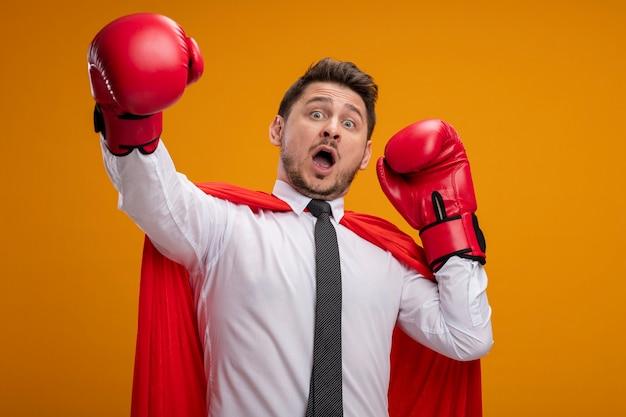 Superbohater biznesmen w czerwonej pelerynie i rękawicach bokserskich przestraszony z rękami stojącymi nad pomarańczową ścianą