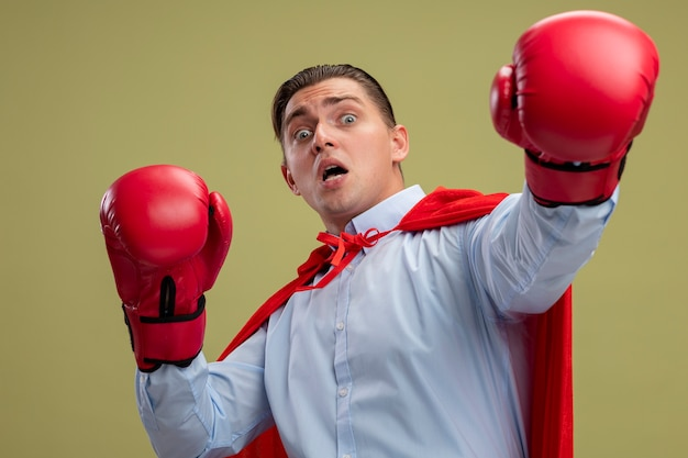 Superbohater biznesmen w czerwonej pelerynie iw rękawicach bokserskich patrząc na kamery przestraszony ręką stojącą na jasnym tle