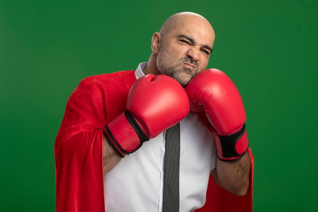 Superbohater biznesmen w czerwonej pelerynie iw rękawicach bokserskich patrząc z przodu z zmieszanym wyrazem stojącym nad zieloną ścianą
