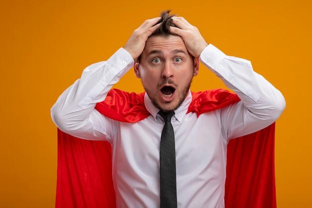 Superbohater biznesmen w czerwonej pelerynie jest szalony, zdumiony, ciągnąc za włosy stojąc na pomarańczowej ścianie