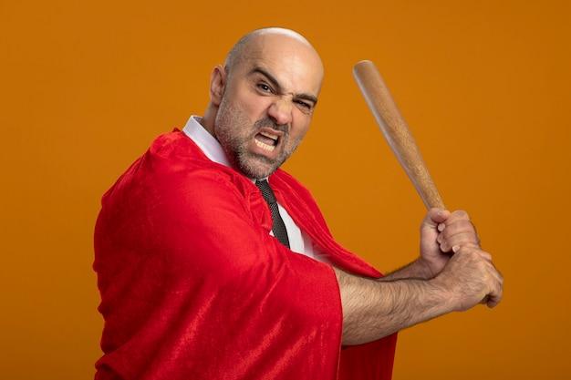 Superbohater biznesmen w czerwonej pelerynie kołyszący kij bejsbolowy patrząc z przodu z gniewnym wyrazem agresywnej stojącej nad pomarańczową ścianą