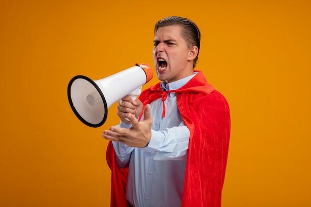 Superbohater biznesmen w czerwonej pelerynie krzyczy do megafonu z agresywnym wyrazem ręki stojącej nad pomarańczową ścianą