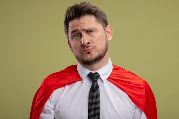 Superbohater biznesmen w czerwonej pelerynie lookign w aparacie ze smutnym wyrazem twarzy stojącej na zielonym tle
