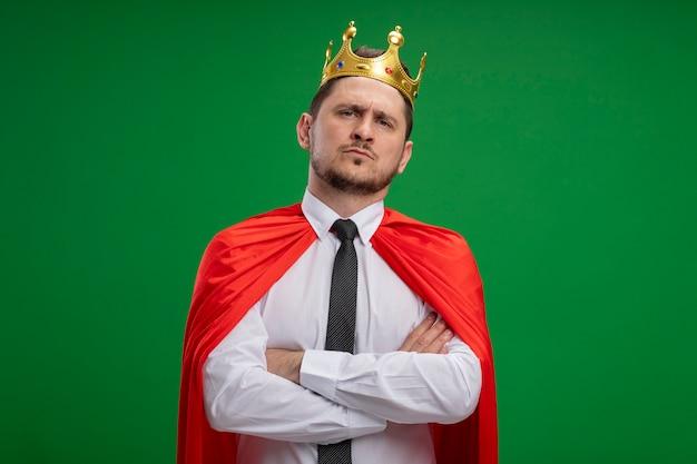 Superbohater biznesmen w czerwonej pelerynie noszącej koronę patrząc na kamery z poważnym wyrazem pewności ze skrzyżowanymi rękami na piersi stojącej na zielonym tle