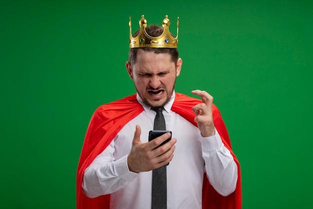 Superbohater biznesmen w czerwonej pelerynie noszącej koronę za pomocą smartfona szalejący wściekły, stojący na zielonym tle