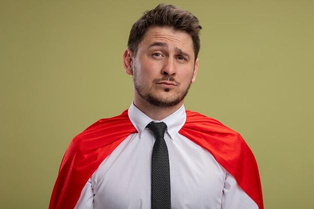 Superbohater biznesmen w czerwonej pelerynie patrząc na kamery, mylić ze smutnym wyrazem stojącym na zielonym tle