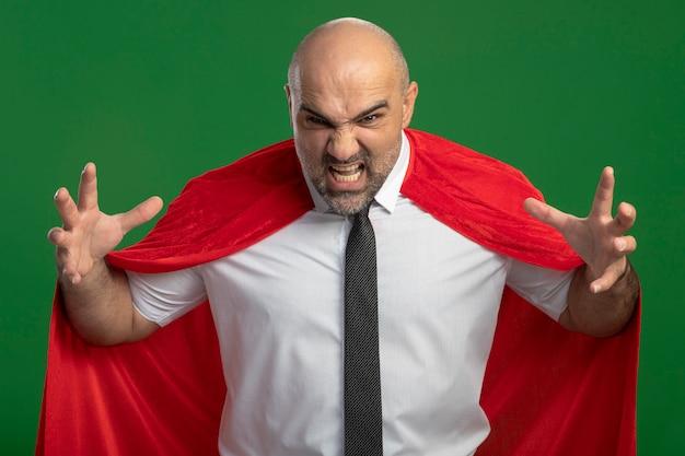 Superbohater biznesmen w czerwonej pelerynie, patrząc na przód wirtha, podnosi ramiona, krzycząc z wściekłą twarzą stojącą nad zieloną ścianą