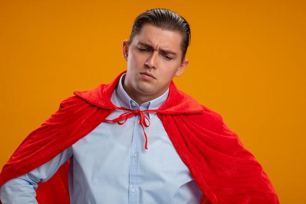 Superbohater biznesmen w czerwonej pelerynie patrząc w dół ze smutnym wyrazem twarzy stojącej nad pomarańczową ścianą