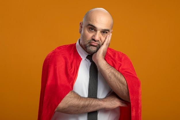 Superbohater biznesmen w czerwonej pelerynie, patrząc z przodu ze smutnym wyrazem twarzy, opierając głowę na dłoni, stojąc na pomarańczowej ścianie