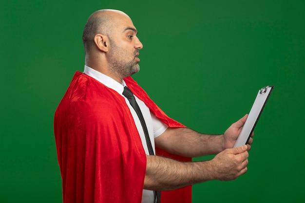 Superbohater biznesmen w czerwonej pelerynie pokazuje schowek z pustymi stronami patrząc na niego z poważną twarzą stojącą nad zieloną ścianą