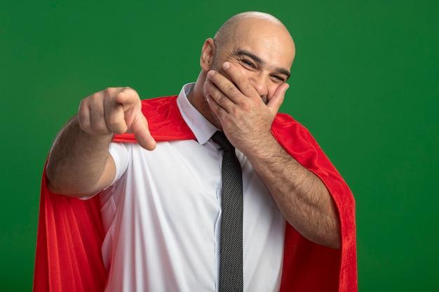 Superbohater biznesmen w czerwonej pelerynie śmiejąc się zakrywając usta ręką wskazując figner indeksu w aparacie