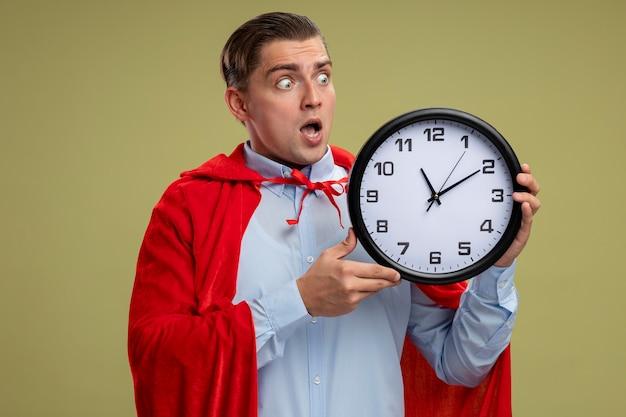 Superbohater biznesmen w czerwonej pelerynie trzyma zegar ścienny patrząc na to, że jest szalony, zdumiony i zaskoczony, stojąc na jasnym tle