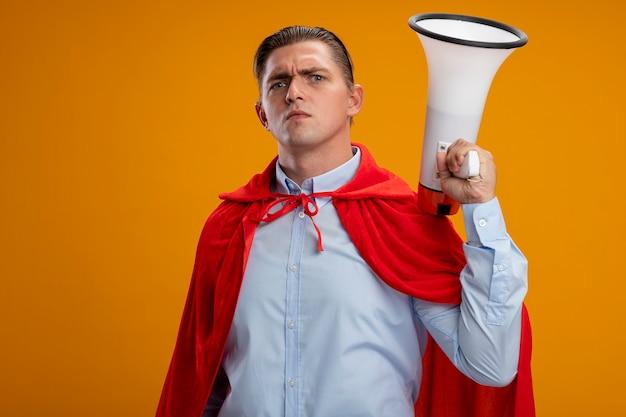 Superbohater biznesmen w czerwonej pelerynie trzymając megafon z poważną zmarszczoną twarzą stojącą nad pomarańczową ścianą