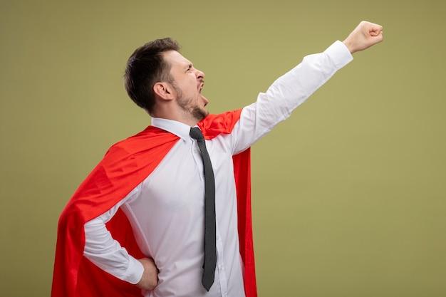 Superbohater biznesmen w czerwonej pelerynie, trzymając ramię w latający gest krzycząc gotowy do walki stojąc na zielonym tle