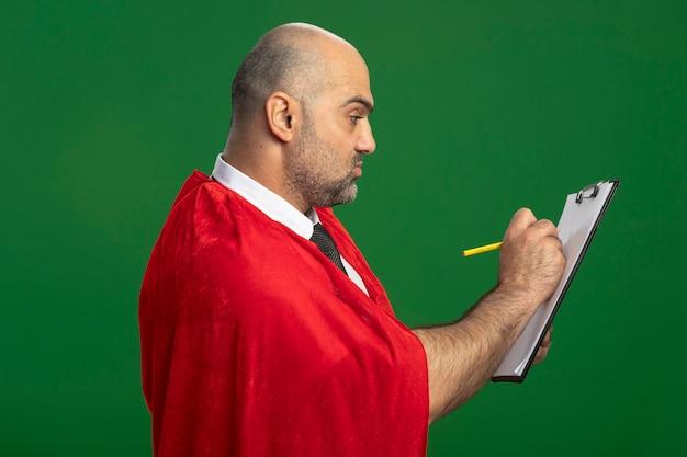Superbohater biznesmen w czerwonej pelerynie trzymając schowek z pustymi stronami, pisząc coś z poważną twarzą stojącą nad zieloną ścianą
