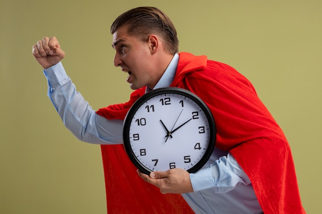 Superbohater biznesmen w czerwonej pelerynie trzymając zegar ścienny pośpiechu działa gotowy do pomocy stojąc na jasnym tle
