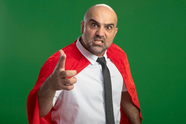 Superbohater biznesmen w czerwonej pelerynie, wskazując palcem wskazującym na aparat, niezadowolony i zły, stojąc na zielonej ścianie