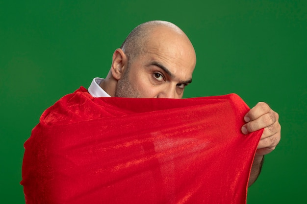 Superbohater biznesmen w czerwonej pelerynie zakrywającej twarz patrząc pewnie stojąc nad zieloną ścianą