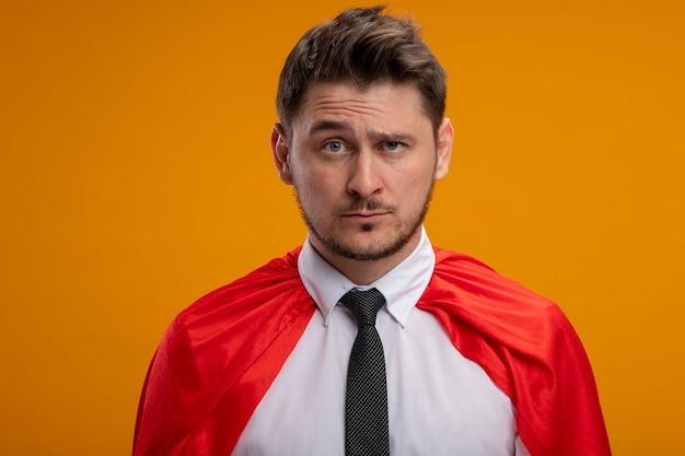 Superbohater biznesmen w czerwonej pelerynie ze smutnym wyrazem stojącym nad pomarańczową ścianą