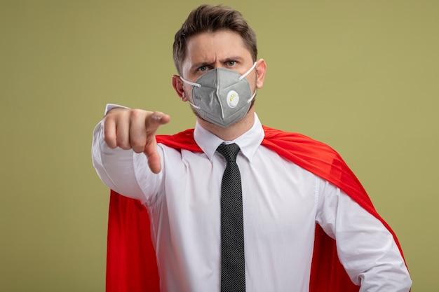 Superbohater biznesmen w ochronnej masce na twarz i czerwonej pelerynie, wskazując palcem wskazującym na ciebie, patrząc pewny siebie niezadowolony stojąc na zielonym tle