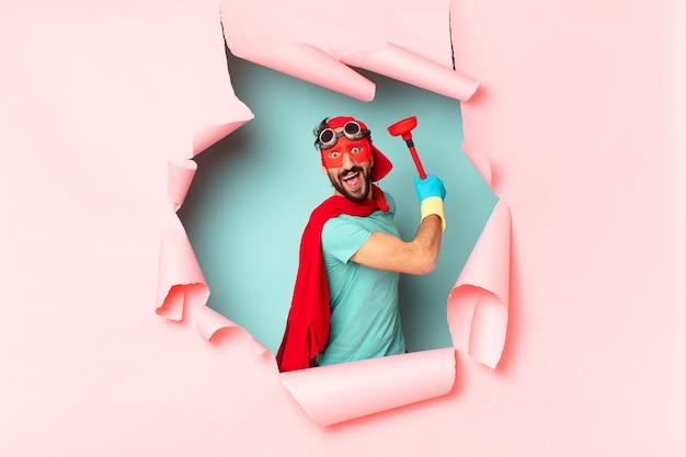 Superbohater z przedmiotami łazienkowymi za połamaną papierową ścianą