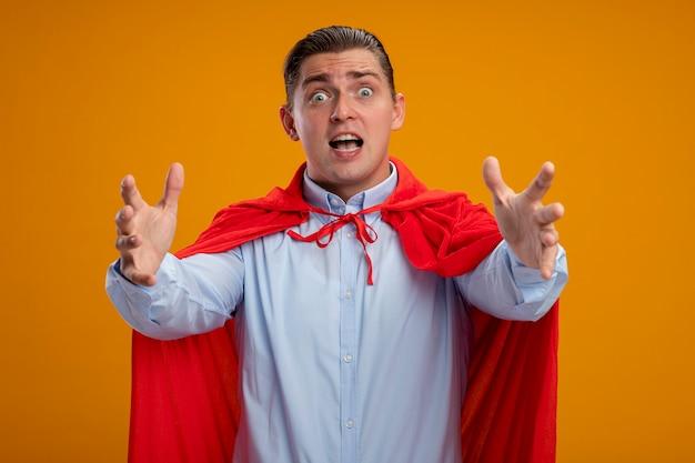 Superbohatera biznesmen w czerwonej pelerynie z szalonym spojrzeniem zaskoczenia, zdumiony i zdziwiony z wyciągniętymi ramionami, stojąc nad pomarańczową ścianą