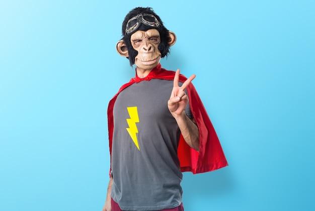 Superhero małpa człowiek robi gest zwycięstwa na kolorowe tło