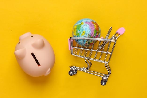 Supermarket gobal. skarbonka i wózek na zakupy, kula ziemska na żółto.
