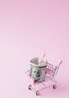 Supermarket koszyk pełen banknotów dolara amerykańskiego na różowym tle z miejsca kopiowania. wolny handel. rynek pieniężny. styl minimalizmu. wózek sklepowy w supermarkecie. sprzedaż, rabat