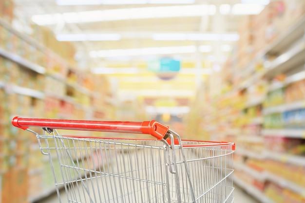 Supermarket nawy niewyraźne tło z pustym czerwonym koszykiem