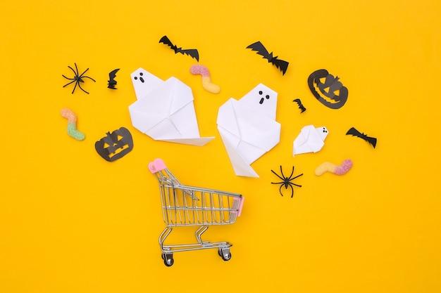 Supermarketowy wózek z dekoracją z ręcznie robionego papieru halloween, gumowate robaki na żółtym tle. widok z góry