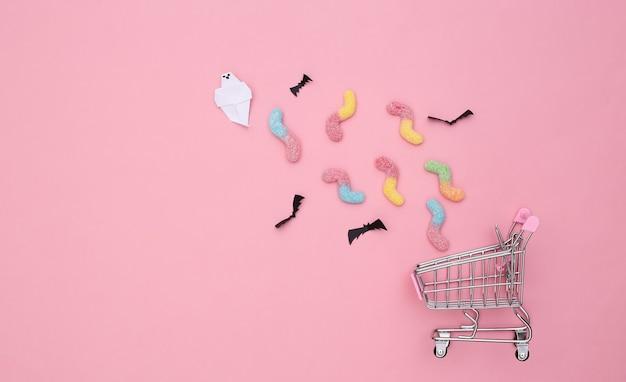 Supermarketowy wózek z ręcznie robionymi nietoperzami i duchem, gumowatymi robakami na różowym pastelowym tle. koncepcja halloween. widok z góry