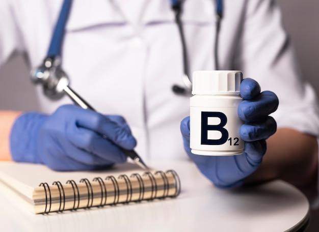 Suplement witaminy b12 w białym słoiku w rękach lekarza w rękawiczkach.