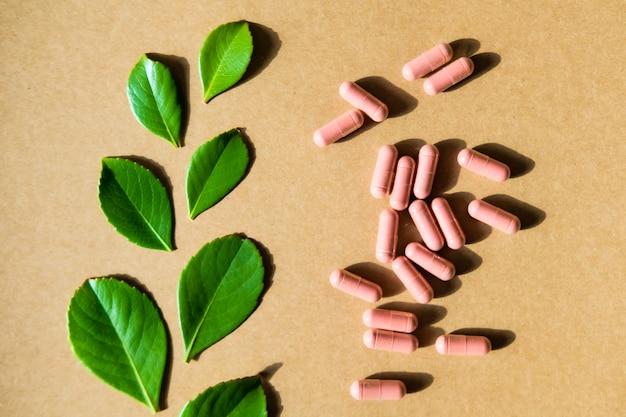 Suplement ziołowy w brązowych kapsułkach i zielonych liściach