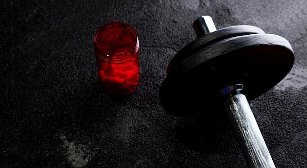 Suplementy sportowe z ciężarkami na ciemnej powierzchni. leki