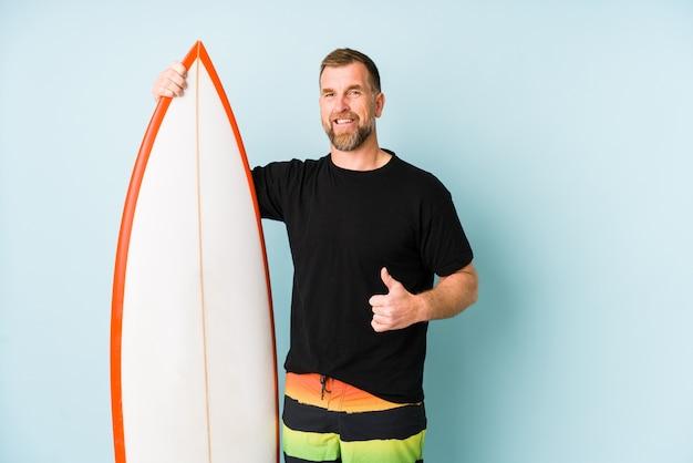Surfen mężczyzna odizolowywający na błękit ścianie uśmiecha się kciuk up i podnosi