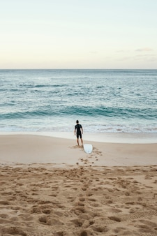 Surfer człowiek patrząc na morze pionowe długie ujęcie